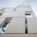 Angled openings create balconies across the facade of MORA apartments by ADNBA