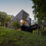 Red Rock House by Anmahian Winton Architects sits on a forested New York hillside