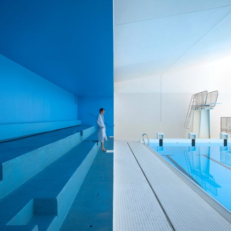 Refurbished Paris swimming pool features blue bleachers and an outdoor sunbathing deck