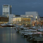 White concrete cultural centre by DRDH nestles up against a Norwegian harbour