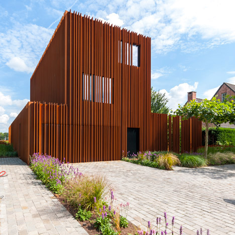 The Corten House by DMOA architecten is surrounded by weathered steel fins