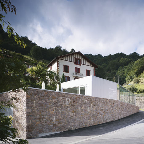 Mining museum by V2S contrasts a traditional stone wall with a metal box