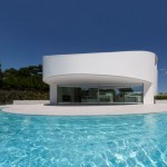 Crescent-shaped pool skirts cylindrical house by Fran Silvestre Arquitectos