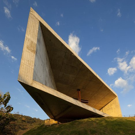 Skewed concrete chapel by EMC Arquitectura balances over a mountainside in El Salvador