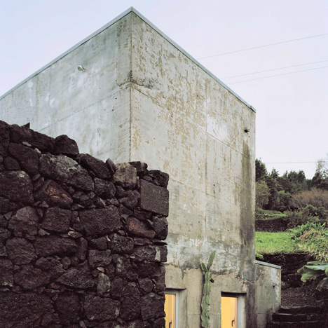 Ageing stone walls frame concrete structure of E/C House by SAMI Arquitectos