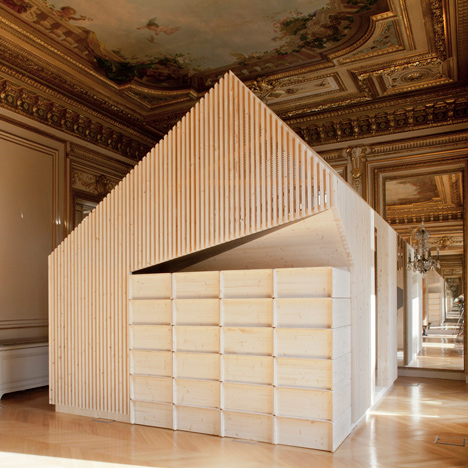 Wooden meeting rooms by Estelle Vincent include seating, lockers and a slide
