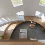 A staircase lands on a desk inside House in Hikone by Tato Architects