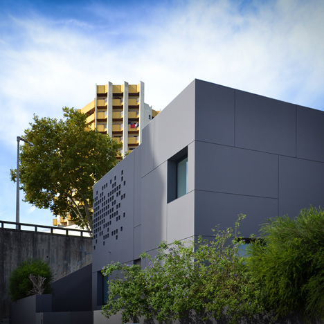 Portuguese office by GGLL Atelier is a grey box punctured by a grid of holes