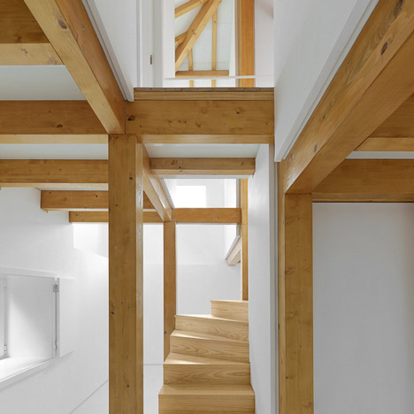 Wooden trusses support new mezzanines inside remodelled stone building by Corpo Atelier