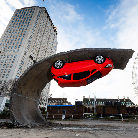 Parked car is upended on a tarmac wave in Alex Chinneck installation