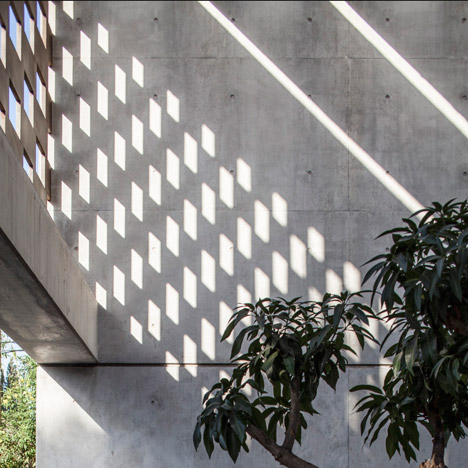Perforated screens cast graphic shadow patterns over concrete house by Pitsou Kedem