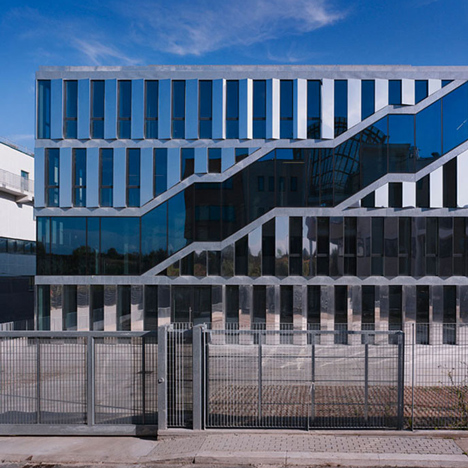 Staircases trace a path across the glazed facade of Intecs office block in Rome