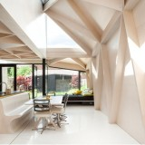 Plywood frames create a pattern of triangles inside house extension by NOJI Architects