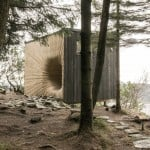 Norwegian mountain hut is entered through a curving wooden orifice