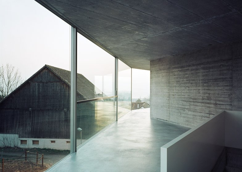 Crooked concrete wall divides a zurich building into two homes
