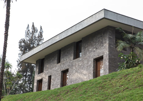 Hewn limestone walls and an overhanging roof enclose a hillside home in Nairobi