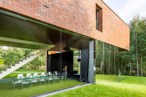 Structure cantilevers over the garden of a Polish house