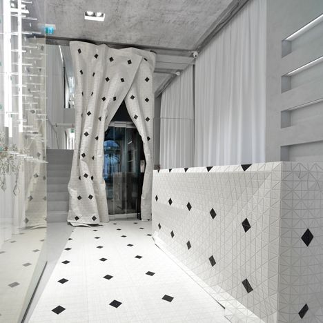 Wooden curtain drapes around a lift inside Maison Margiela's Milan store