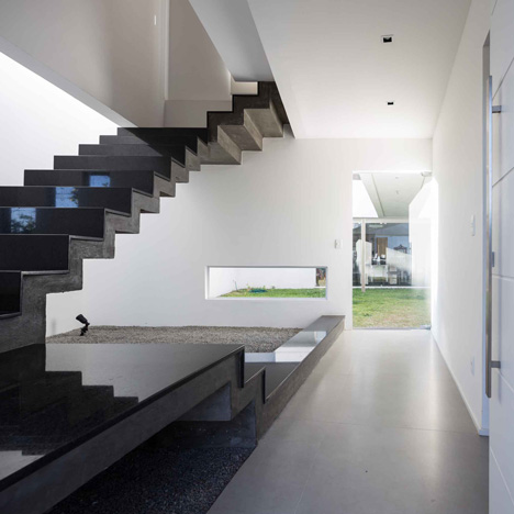 Casa 2V by BR3 Arquitetos features a bridge, a courtyard and a granite-topped staircase