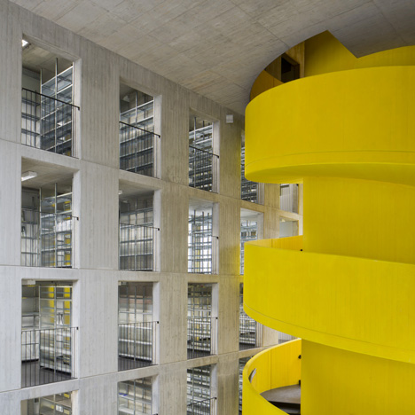 Baukuh's House of Memory features a decorative facade and a monumental yellow staircase