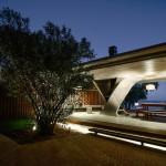 Lakeside concrete pavilion by NE-AR houses a fireplace inside a twisted column