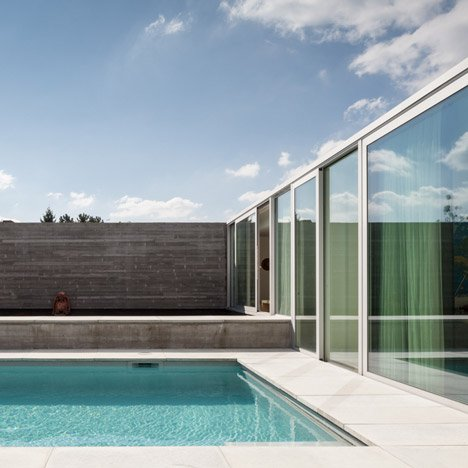 Concrete and glass extension to Belgian house shelters a poolside patio