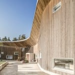 Curving wooden wall fronts Ruukki Health Clinic in Finland by Alt Arkkitehdit