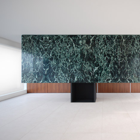 Monolithic marble partition perches on top of a steel fireplace in Antwerp penthouse