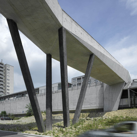 Faceted concrete bridge by 2b Architectes links a metro station with a forest