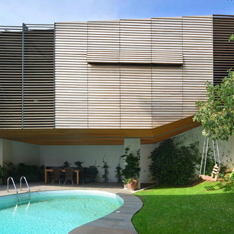 Hiboux Architects elevates slatted timber garage above the pool of an Athens house