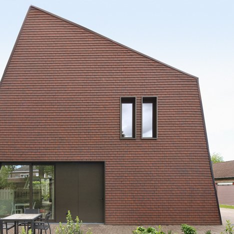 Villa Willemsdorp by Dieter De Vos features a lopsided gable and walls clad with roof tiles