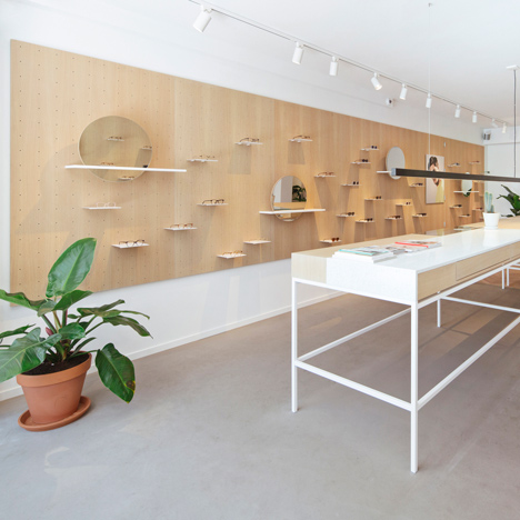 Wooden pegboard lines the walls within Ace & Tate's Amsterdam eyewear store