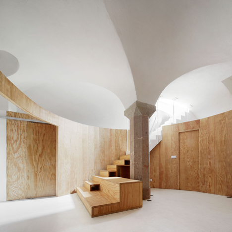Circular pine wall creates rooms in vaulted basement home by Raúl Sánchez