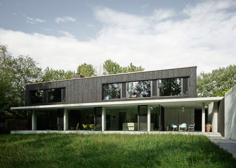 Concrete slabs frame glass walls of Swiss house by MLZD