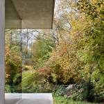 Slabs of concrete frame glass walls of house near a Swiss lake by MLZD