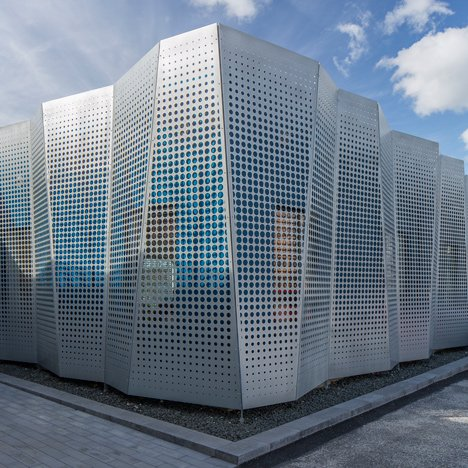 Perforated metal sheets concertina across the facade of an office extension in Lund