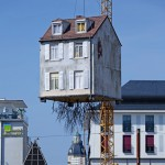 Roots trail from house suspended above a construction site by Leandro Erlich