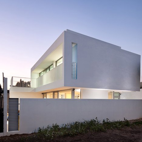 172M2 House by JMY Architects maintains privacy with a blank facade and a secluded garden