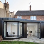 Blackened timber extension by Scenario Architecture features a high walkway for cats