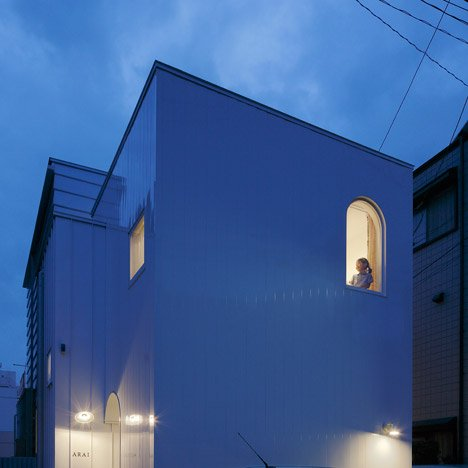 Arched openings cut through walls of Takushu Arai's steel-plated house in Yokohama