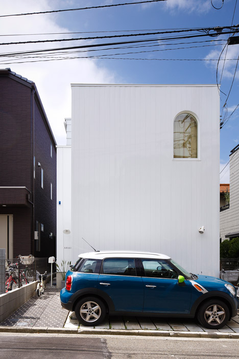 Arched openings cut through walls of Takushu Arai's steel-plated house in Yokohama