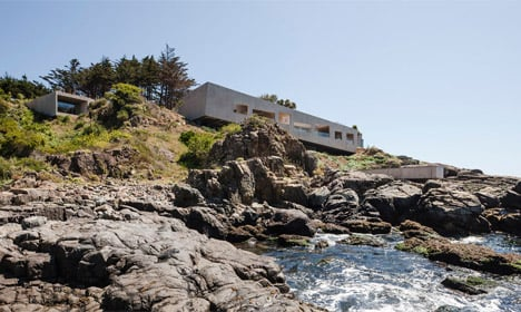 Concrete painter's studio by Felipe Assadi nestles into a rocky hillside on the Chilean seafront