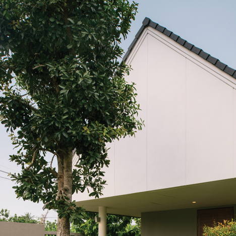 Triangle House in Thailand features gabled walls, a courtyard and a lily pond