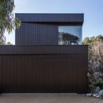 Blackened timber boxes are stacked to provide sea views from Bass Street Residence