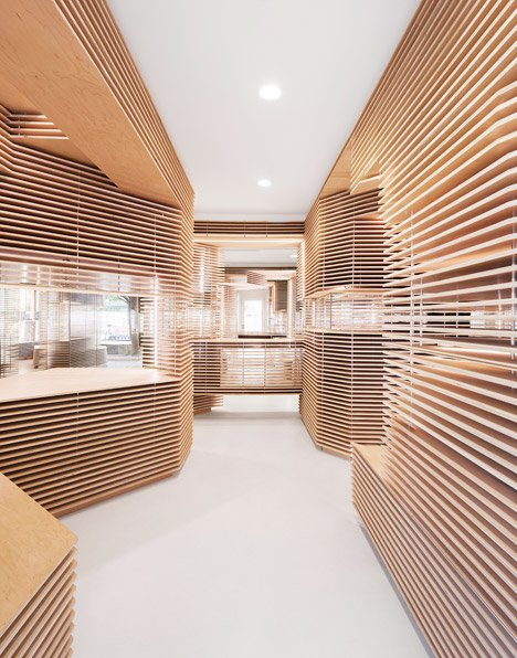 Floating timber slabs create layered walls within New York shoe store by Jordana Maisie