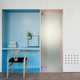 Wall of hidden panels provides storage for renovated Tel Aviv apartment
