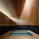 Kubo Tsushima Architects creates curved cedar interior inside Japanese bathhouse