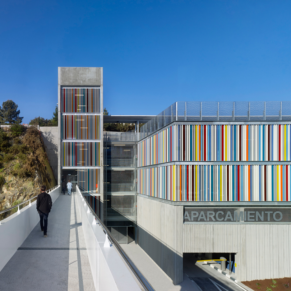 Coloured metal slats and textured concrete panels enclose hospital car park in Spain