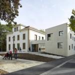 Raw concrete contrasts with 19th-century details at Le Gazouillis kindergarten