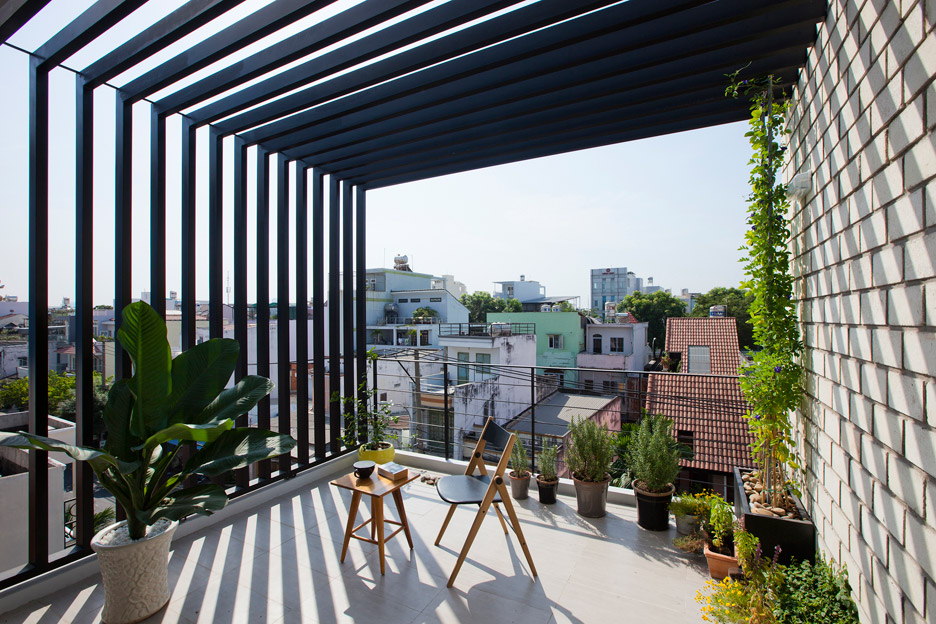 Townhouse with a folding-up shutter in Vietnam by MM++ Architects